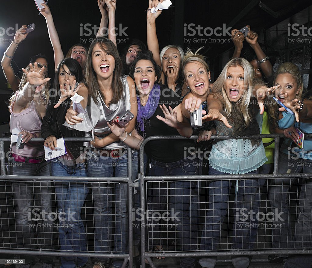 Fans Leaning Over Barrier stock photo