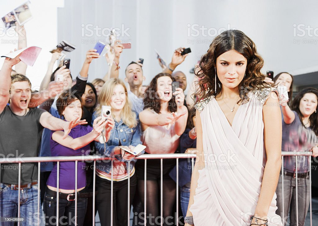 Fans reaching towards celebrity on red carpet stock photo