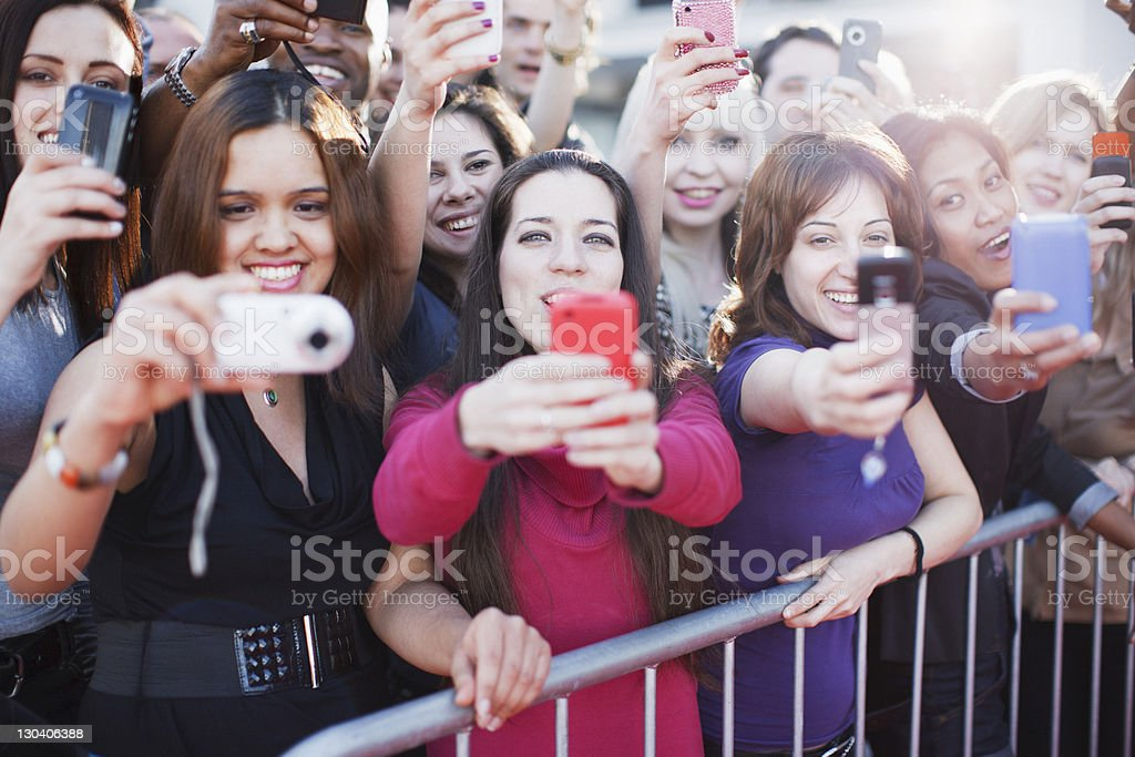 Fans taking pictures with cell phone behind barrier stock photo