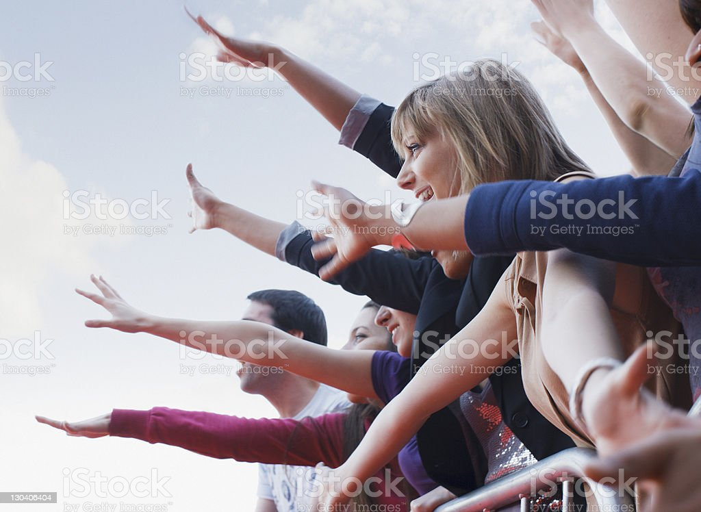 Fans waving from behind barrier stock photo