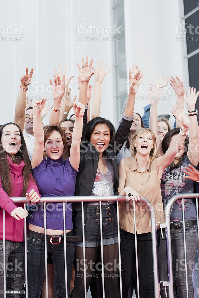 Fans waving from behind barrier royalty-free stock photo