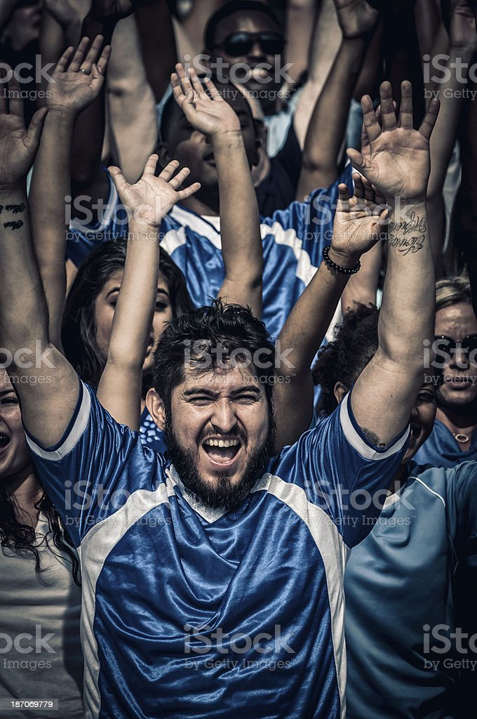 Fans with raised arms cheering for their team royalty-free stock photo