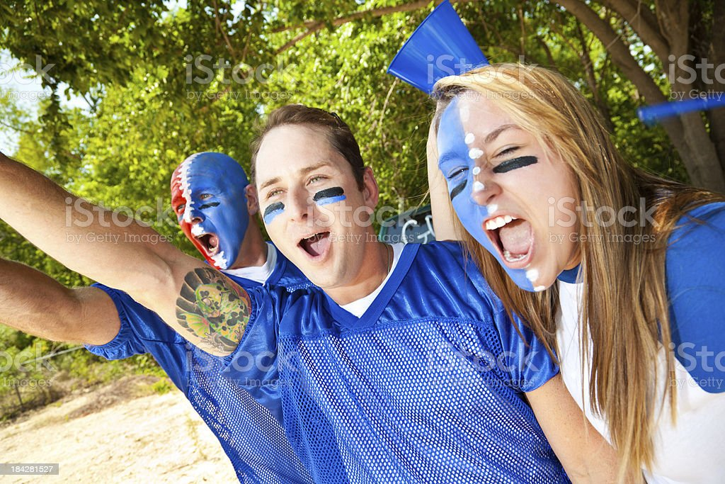 Fans yelling at an outdoor tailgate party royalty-free stock photo
