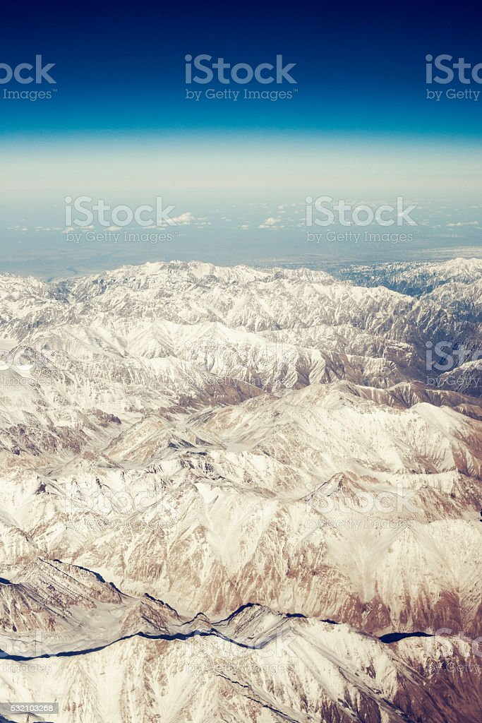 Fantastic background with clouds and mountain peaks stock photo