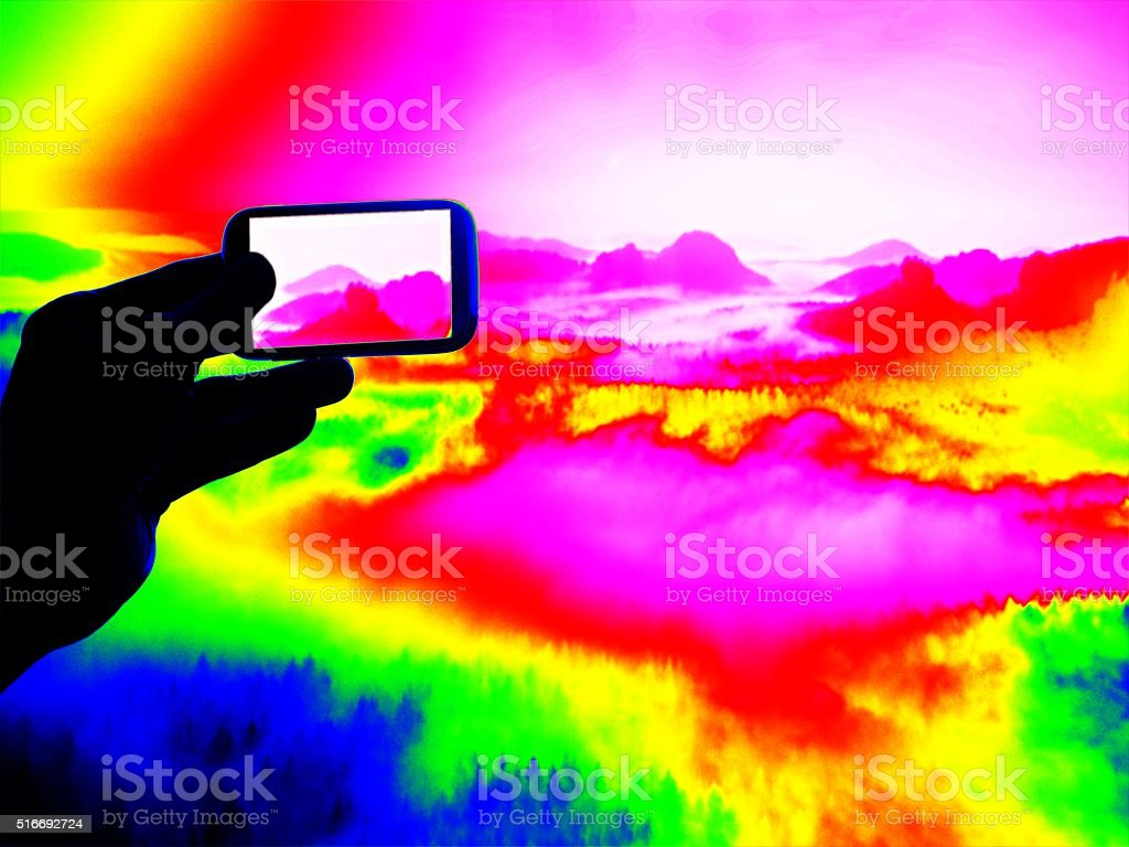 Fantastic infrared scan. Tourist hand takes photos by smartphone stock photo