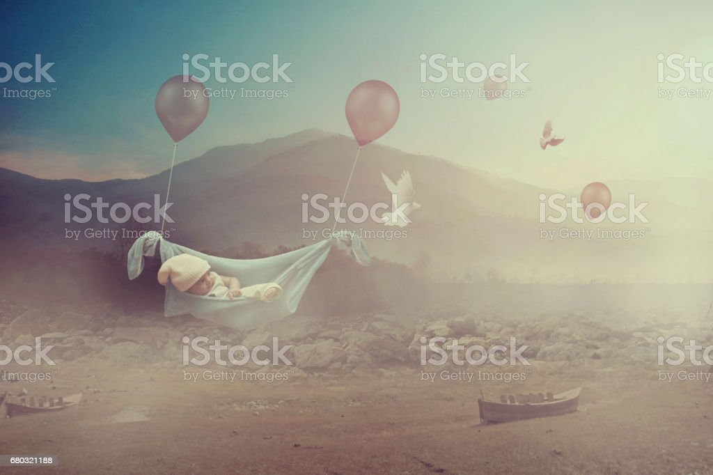 Fantasy - Adorable baby flying with balloons in a valley stock photo