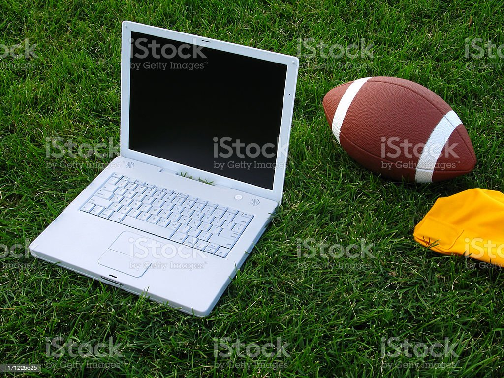 Fantasy Football Concept: Laptop Computer and Football on Grass Field stock photo