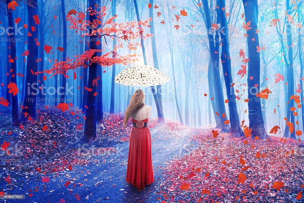 Fantasy lonely woman with umbrella walking in forest stock photo