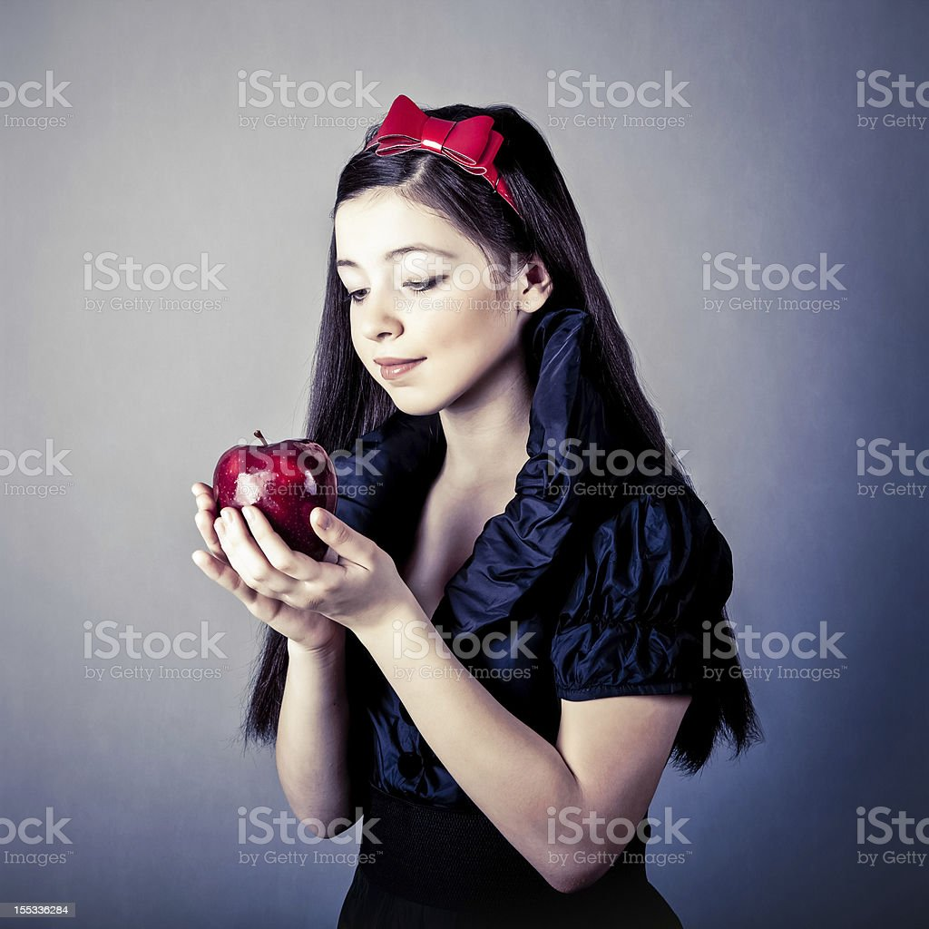 Fantasy portrait of beautiful Snow White holding red apple stock photo