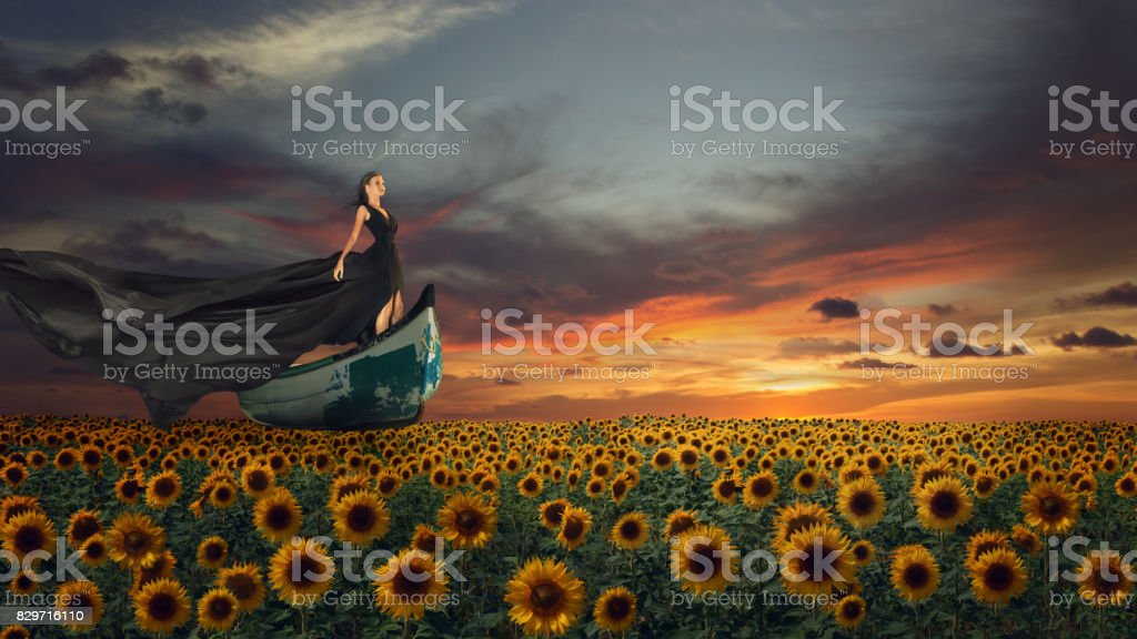 Fantasy portrait of young woman in black dress on the boat stock photo