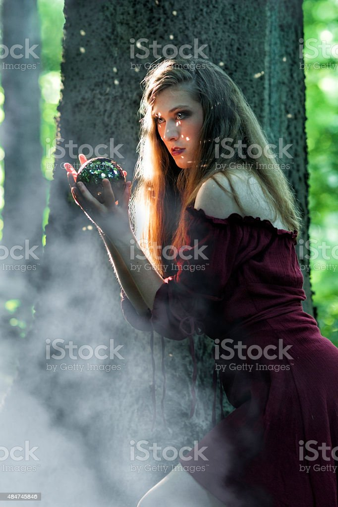 Fantasy scene of woman with sparkling ball in forest stock photo
