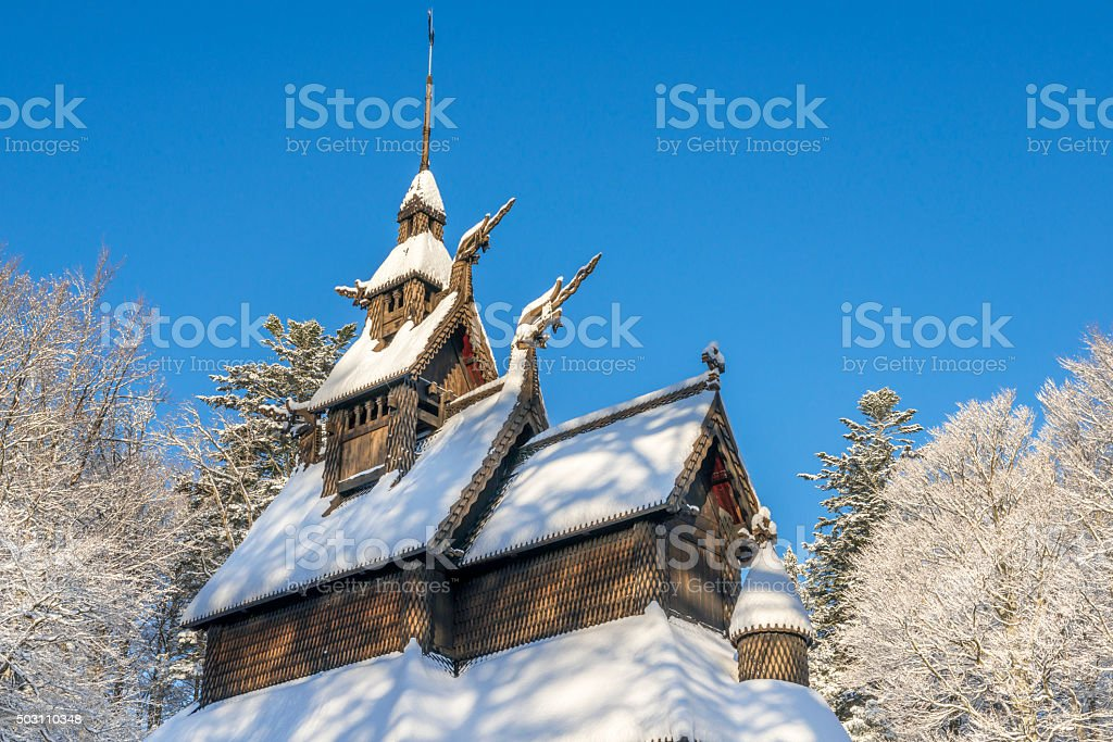Fantoft Stave Church and tall trees in winter after snowfall stock photo