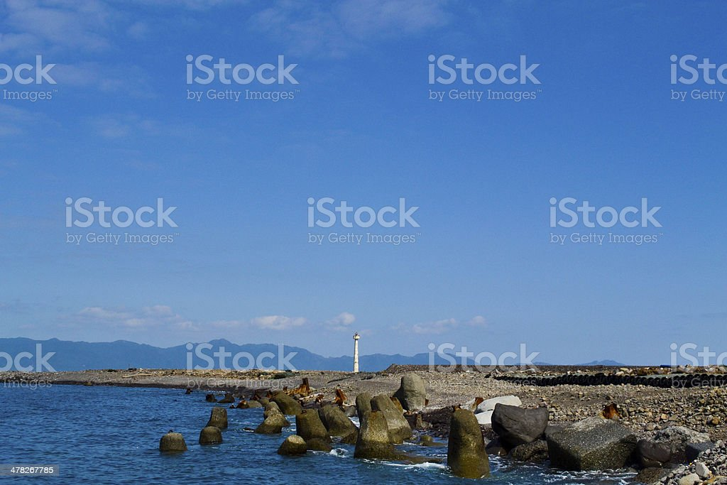 Far away lighthouse under the blue sky royalty-free stock photo