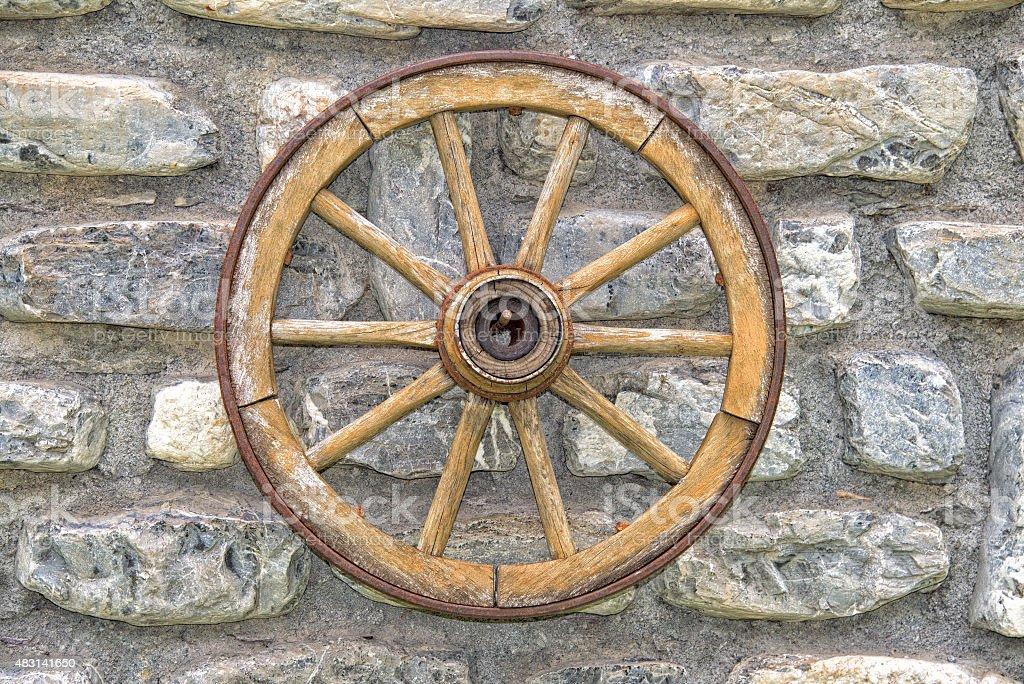 Far west wagon wheel on stone wall stock photo