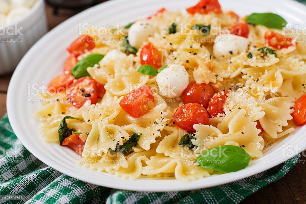 Farfalle Pasta - Caprese salad with tomato, mozzarella and basil stock photo
