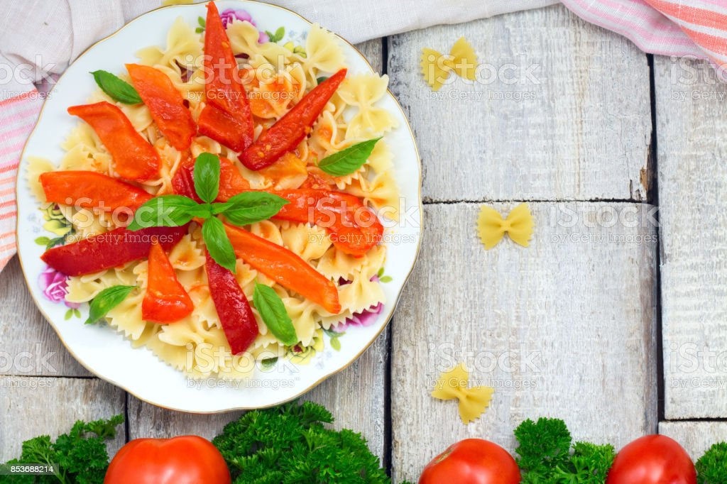 Farfalle Pasta with tomato, pepper and dasil on rustic wooden background with copy space stock photo