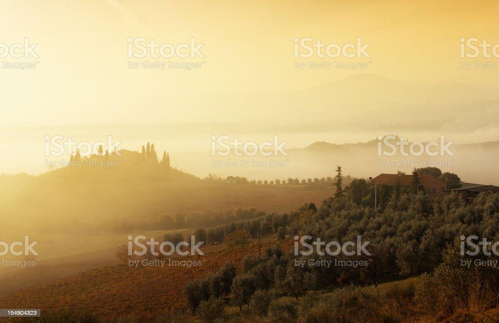 Farm between the foggy hills of Tuscany royalty-free stock photo