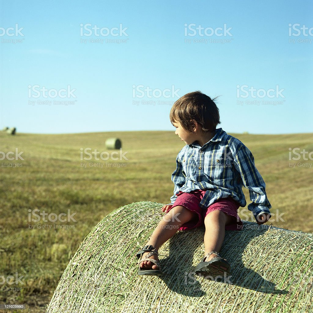 Farm boy on a hay bale in late afternoon sun royalty-free stock photo