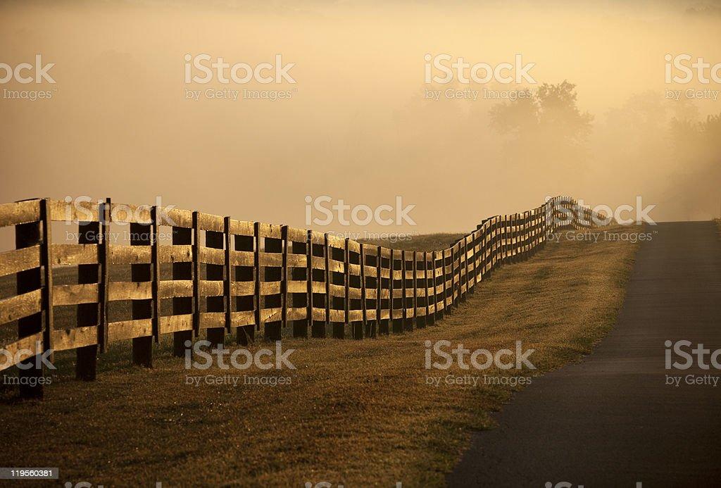 Farm Fence at sunrise with fog stock photo