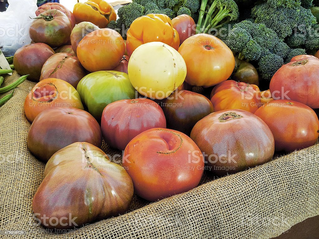 Farm fresh heirloom tomatoes and broccoli on a Farmers Market. stock photo
