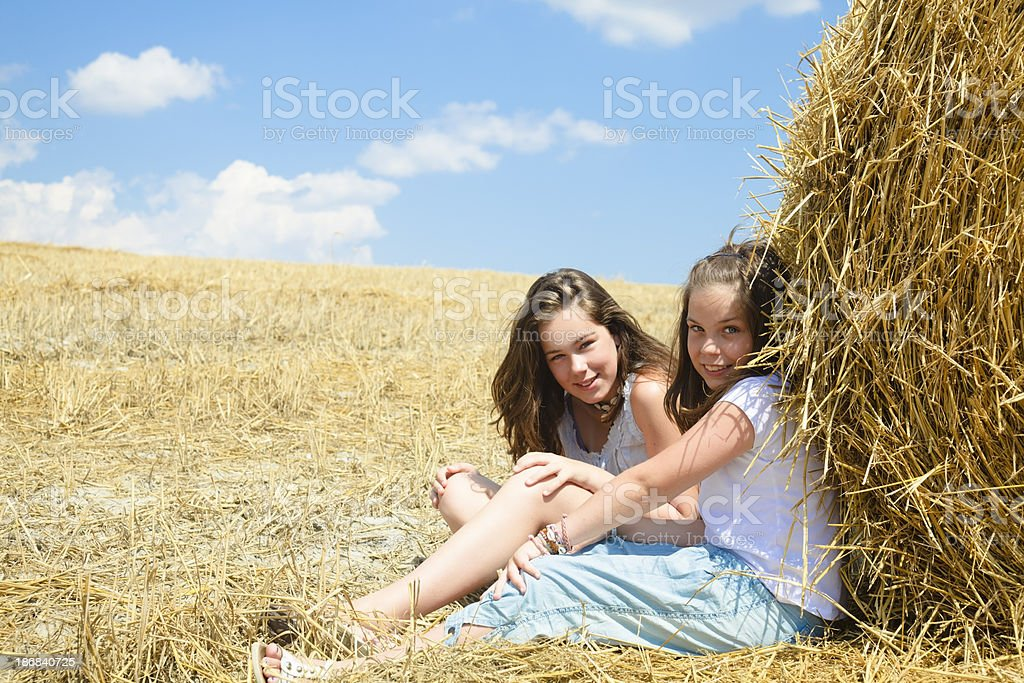 Farm girls and hay bale royalty-free stock photo