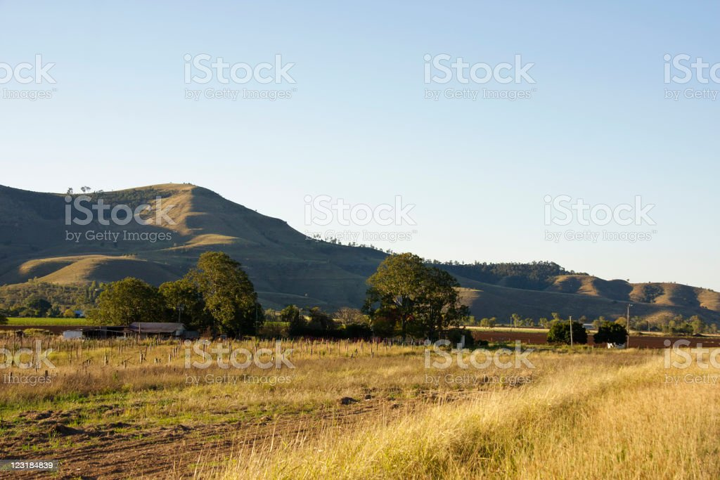 Farm house in front of rolling hills in afternoon shadow royalty-free stock photo