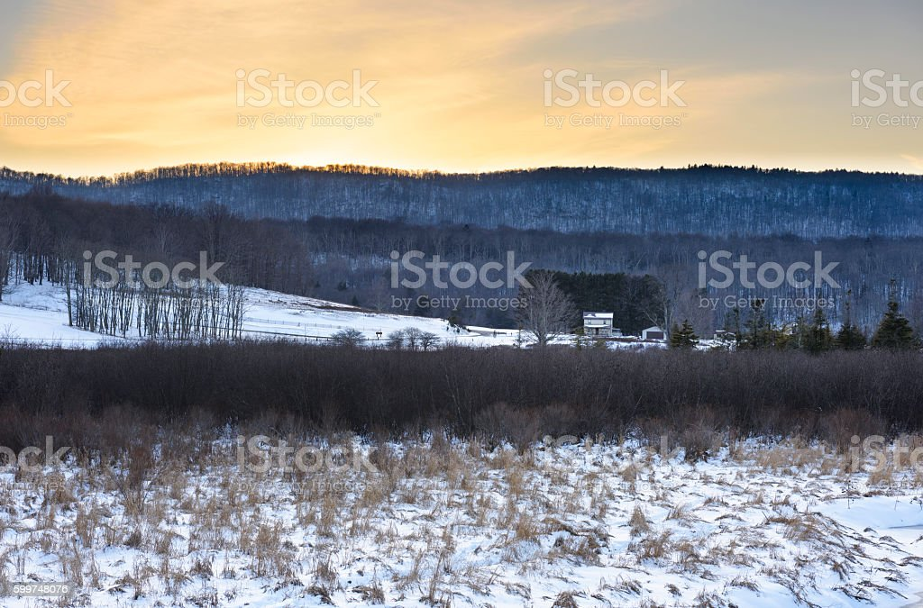 Farm in Winter with View of Mountains stock photo