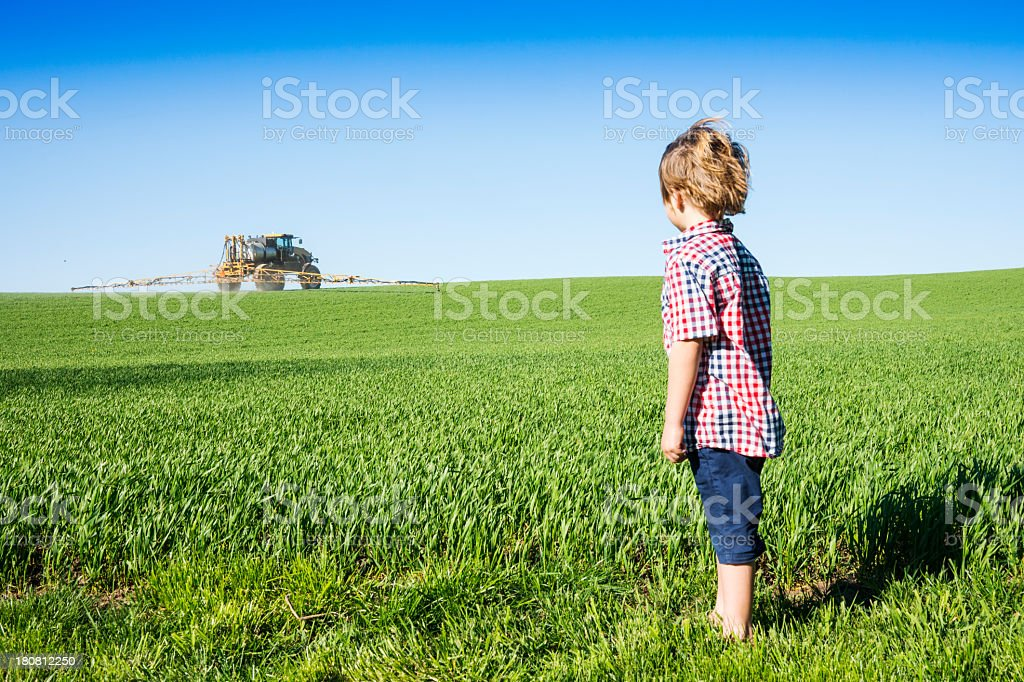 Farm kid looking at a crop sprayer stock photo