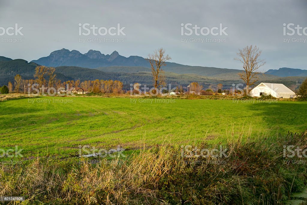 farm landscape with mountains in the background stock photo