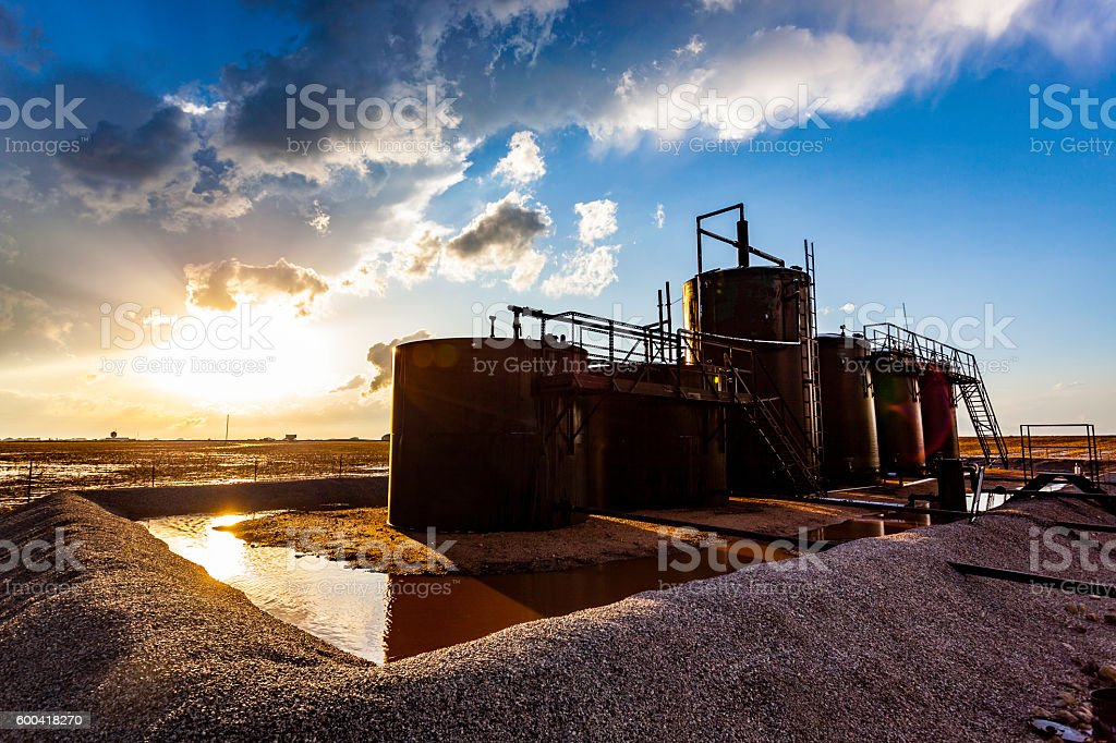 Farm oil storage tanks with stormy sunset and sunflare stock photo