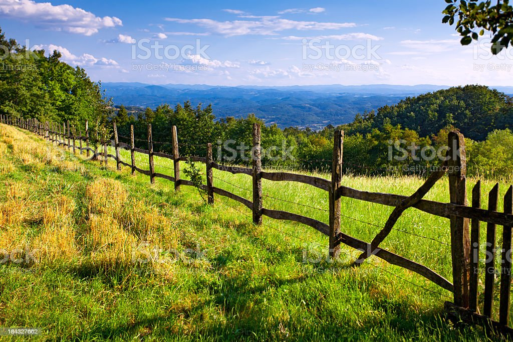 Farm pasture surrounded by a wooden fence stock photo