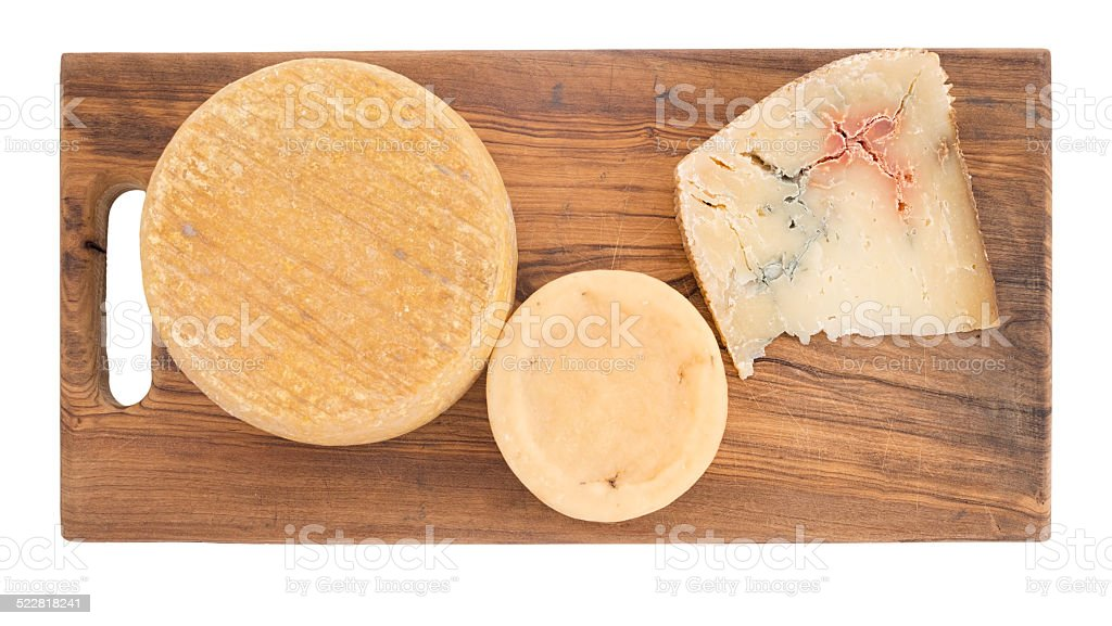 Farm produced rustic cheese including blue, on cheeseboard. Isolated. stock photo