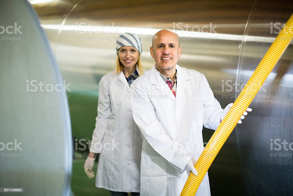 Farm staff with milk cisterns in plant stock photo