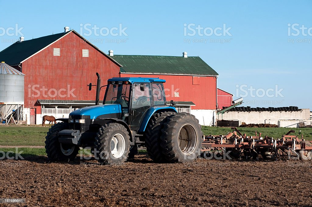 Farm Tractor Cultivating by Barn royalty-free stock photo