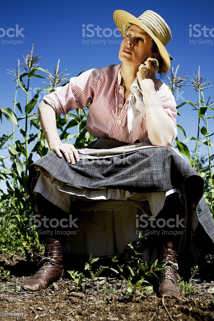 Farm Woman Sits and Pulls up Skirt on Hot Day royalty-free stock photo