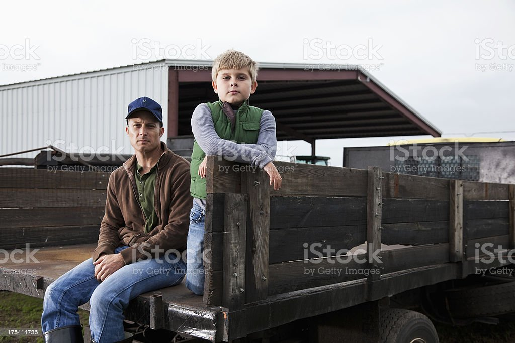 Farmer and son sitting on back of truck stock photo