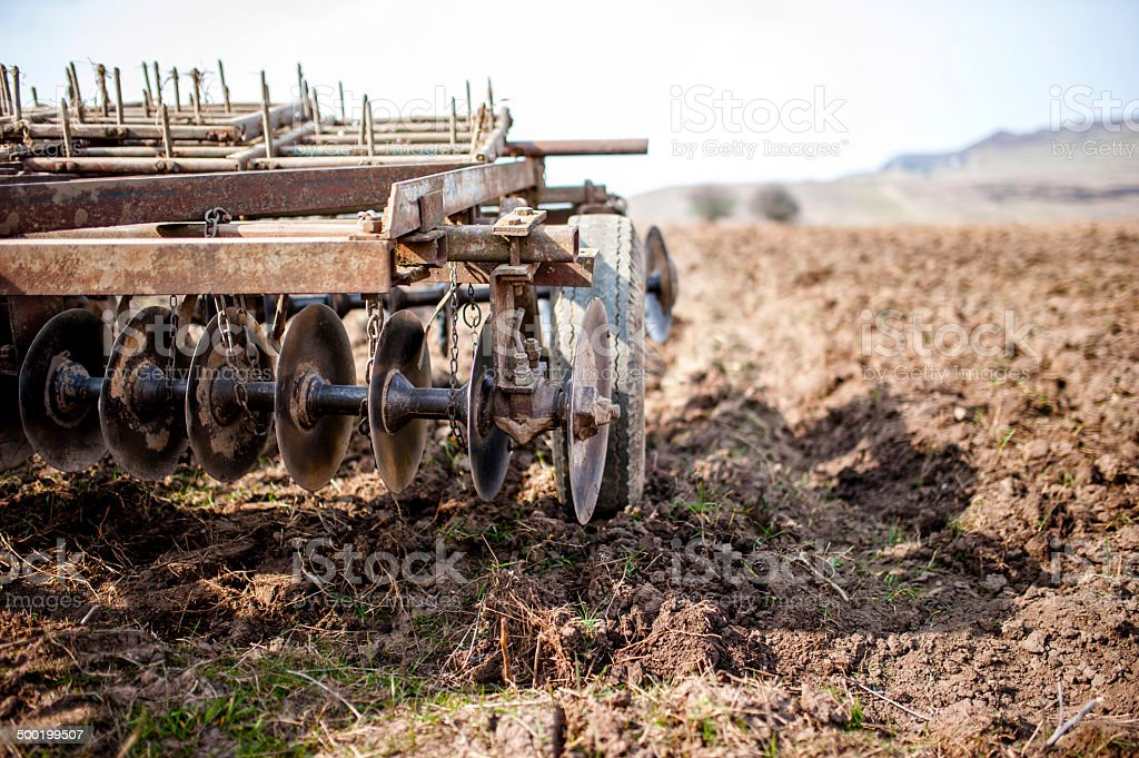 Farmer and tractor with plough, plowing in a field stock photo