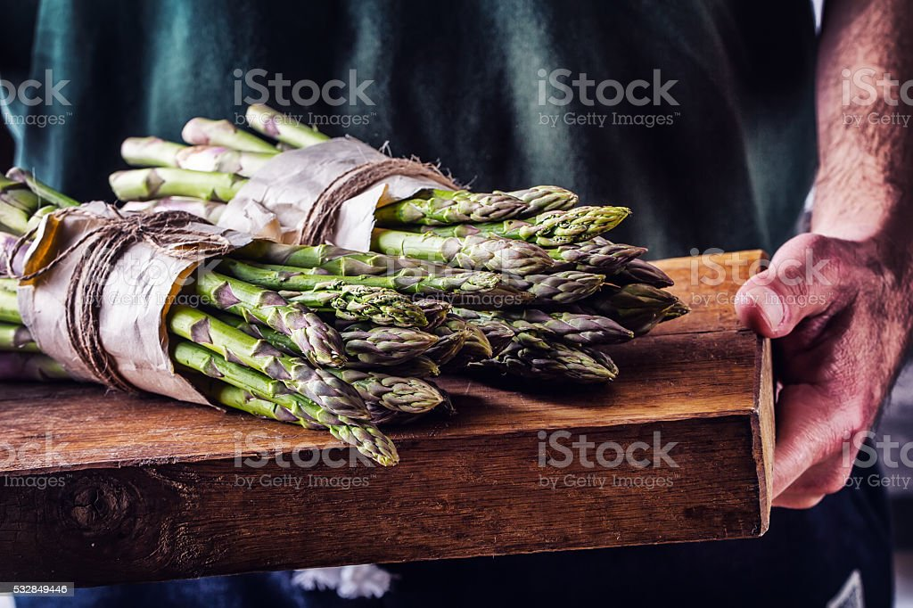 Farmer carries tied asparagus on a wooden board stock photo