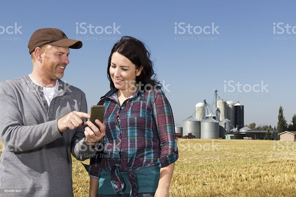 Farmer Couple with Smartphone stock photo