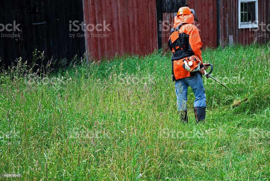 Farmer cutting grass at his barn stock photo