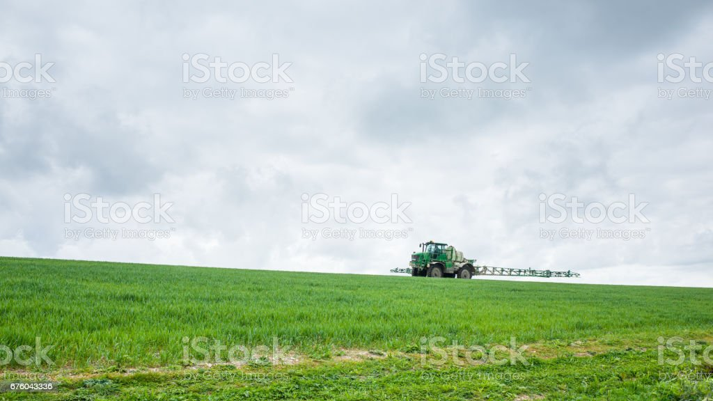 Farmer Drives Crop Spraying Tractor on Field stock photo