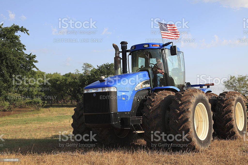 Farmer driving a tractor with American Flag stock photo