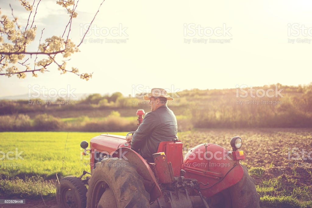 Farmer driving through farm stock photo