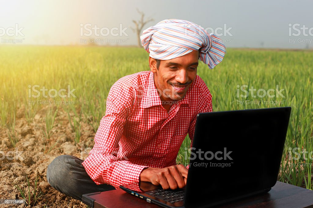 Farmer Enjoying Laptop In Wheat Field stock photo
