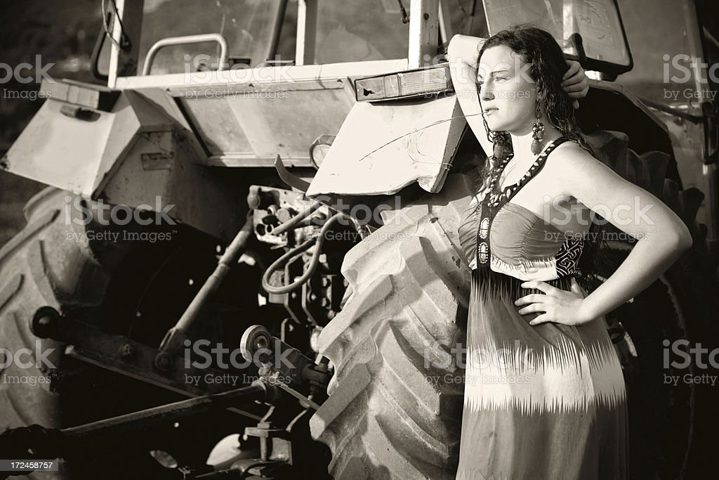 Farmer Girl leaning on a tractor... royalty-free stock photo