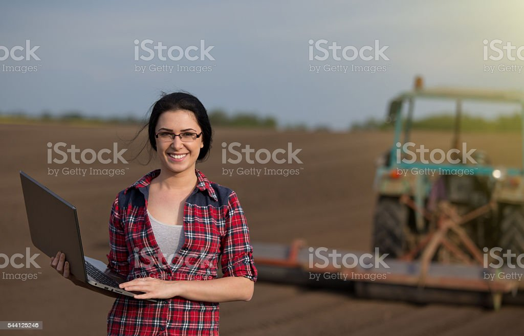 Farmer girl with laptop in field with tractor stock photo