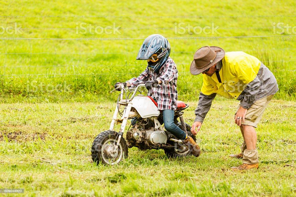 Farmer Helping Bogged Learner Trail Bike Rider on a Farm stock photo