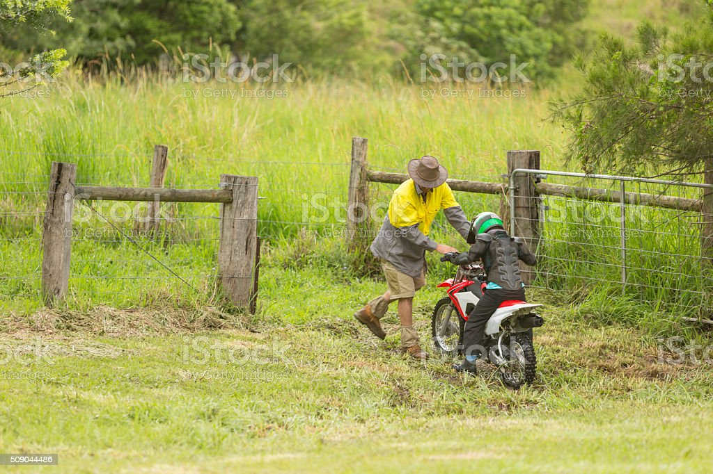 Farmer Helping Bogged Trail Bike Rider on a Farm stock photo