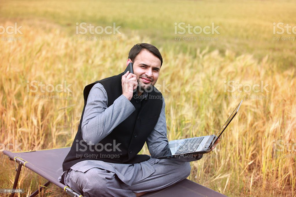 Farmer holding laptop and talking on smartphone stock photo