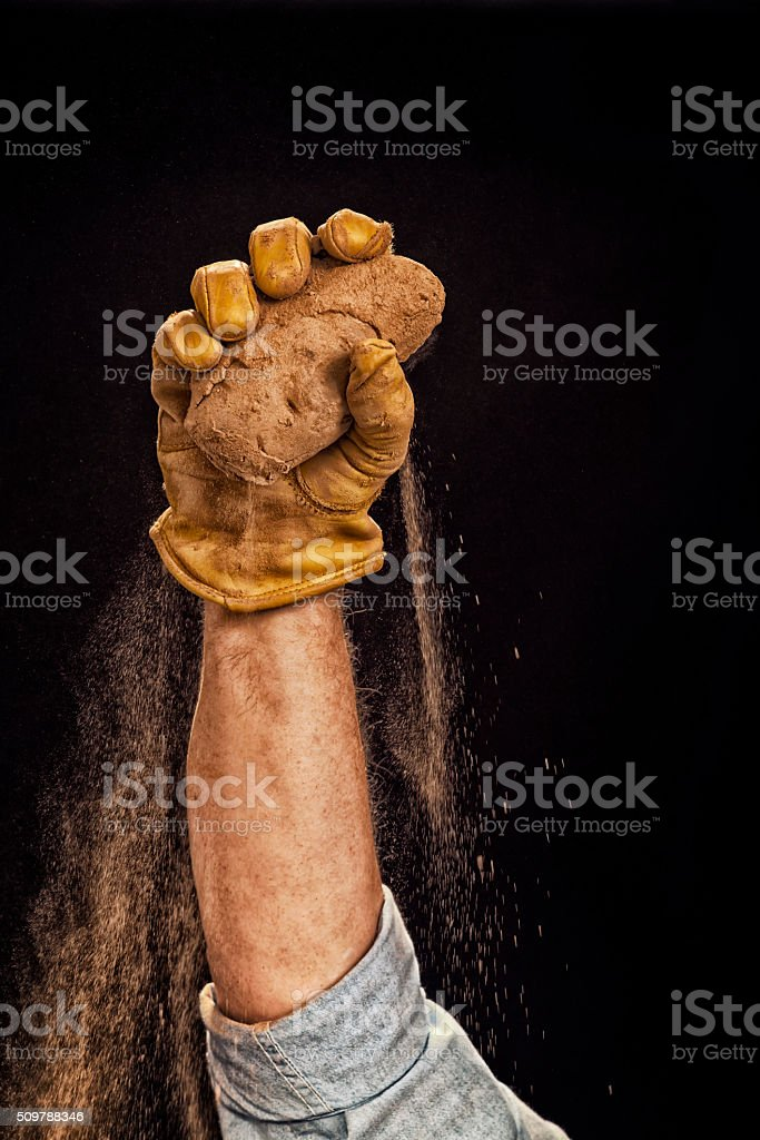 Farmer holding potato in the air against a black background stock photo